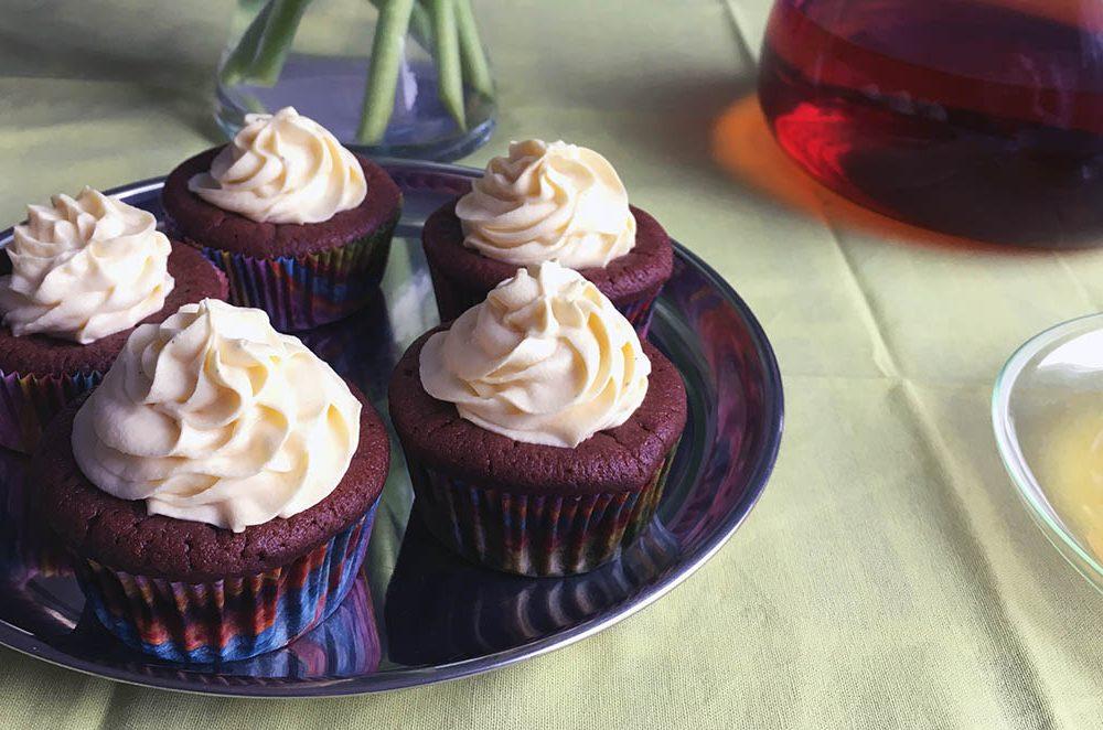 Cupcaky s vanilkovým krémem (5 cupcaků na tácu na jídelním stolu). V pozadí část vázy s tupilány a konvice s čajem).